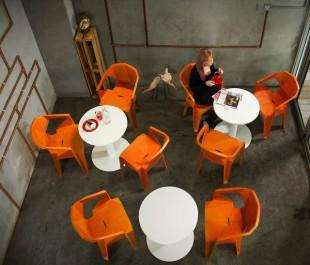 Designerskie pomarańczowe krzesła z podłokietnikami i stoły na jednej nodze z okrągłym blatem