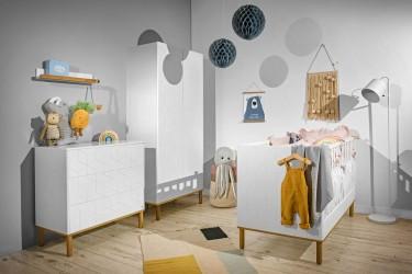 Białe meble dziecięce na drewnianych nóżkach z frontami zdobionymi wzorem geometrycznym