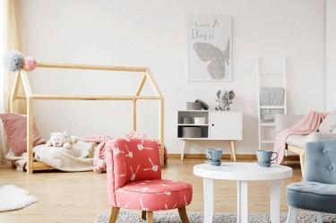 Pokój dziecięcy z kolorowymi fotelikami i okrągłym stolikiem w kolorze białym