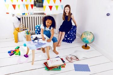 Kwadratowy stolik na drewnianych nogach i kolorowe siedziska do pokoju dziecka
