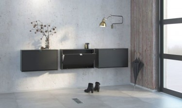 Czarne szafki wiszące na obuwie o matowym wykończeniu na tle jasnej ściany oraz podłogi