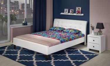 Białe łóżko z tapicerowaną szafką nocną w stylowej sypialni