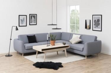 Skandynawski salon z dużą kanapą narożną w kolorze szarym i bielonym stolikiem