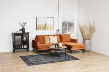 Pomarańczowa kanapa narożna tapicerowana welurem w salonie z czarnymi meblami