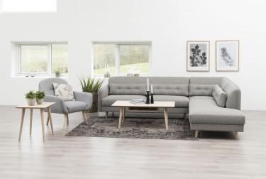 Duży salon w stylu skandynawskim z tapicerowanym narożnikiem szarym i fotelem