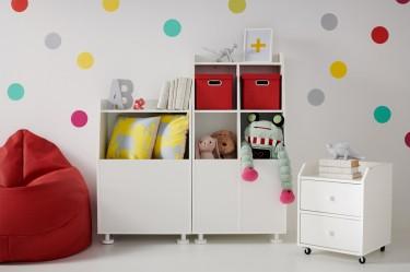 Białe meble w pokoju dziecięcym na tle ściany z kropkami