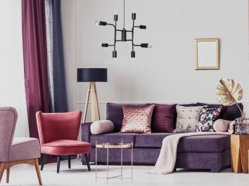 Nowoczesny pokój dzienny z fioletowym narożnikiem i fotelami typu uszak