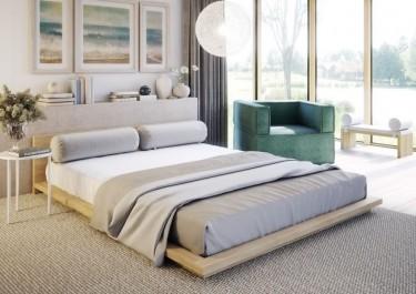 Niskie łóżko na szarym dywanie w sypialni z dużym oknem i jasnymi ścianami