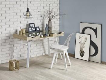 Biurko ze szklanym blatem w towarzystwie krzesła z tapicerowaną poduszką w otoczeniu szarej i ceglanej ściany