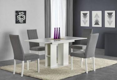 Zestaw mebli z rozkładanym stołem i tapicerowanymi krzesłami na kremowym dywanie w domowej jadalni