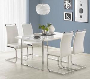 Tapicerowane ekoskórą krzesła u boku lakierowanego na wysoki połysk stołu w modnej jadalni z oknem i długą firaną