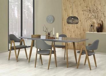 Rozkładany stół z lakierowanym blatem i krzesła tapicerowane ekoskórą  w jadalni z popielatymi ścianami