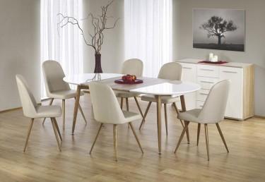 Rozkładany stół z owalnym blatem i krzesła z ekoskóry w jadalni z komodą oraz obrazem na tle popielatej ściany