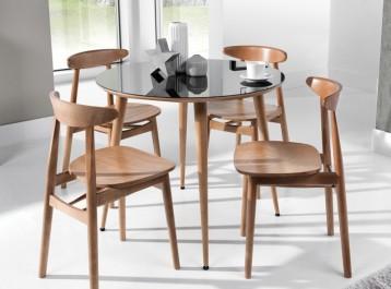 Okrągły stół ze szklanym blatem w towarzystwie drewnianych krzeseł na nogach