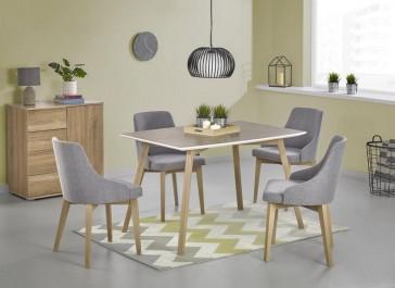 Nierozkładany stół z fornirowanym blatem w towarzystwie szarych krzeseł na drewnianych nogach w stylu skandynawskim