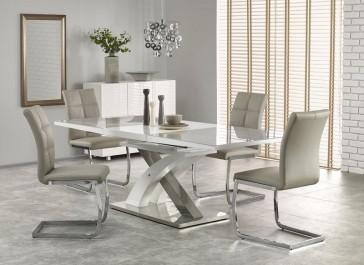 Biało - szary stół ze szklanym blatem na ozdobnej nodze w kształcie litery X i krzesła na płozach bez podłokietników