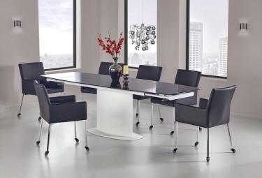 Stół z rozkładanym blatem i krzesłami na kółkach w nowoczesnej jadalni z modnym żyrandolem i oknami