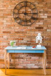 Romantyczne biurko z drewnianymi nogami w stylu skandynawskim na tle ceglastej ściany