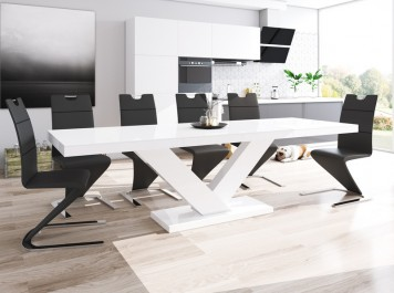 Biały stół rozkładany do 2,5 metrów o połyskującej powierzchni i czarne krzesła z ekoskóry w jadalni połączonej z salonem i kuchnią