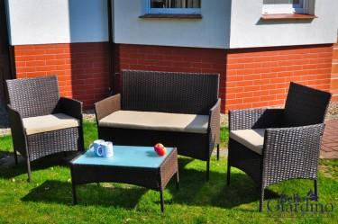 Zestaw brązowych mebli technorattanowych ze stolikiem szklanym w przydomowym ogródku