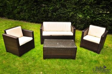 Technorattanowy zestaw mebli z sofą, fotelami i stolikiem w zielonym ogrodzie