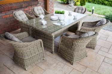 Beżowy zestaw mebli ogrodowych z miękkimi poduszkami dla sześcioosobowej rodziny na przydomowym tarasie