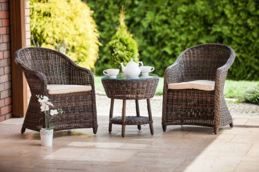 Wygodne fotele z poduszkami oraz stolik kawowy z przeszklonym blatem i praktyczną półką na tarasie
