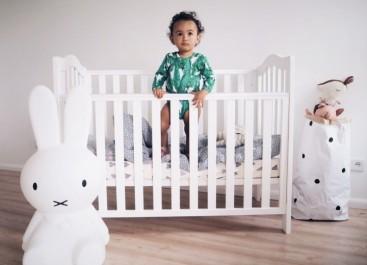Drewniane łóżeczko dziecięce z opuszczaną ramką w pokoju z białymi ścianami i drewnianą podłogą
