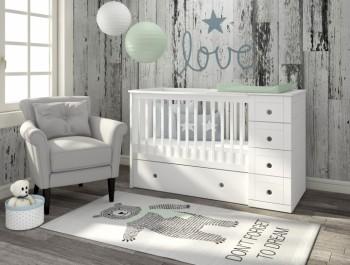 Białe łóżeczko z przewijakiem i szufladami w nowoczesnym pokoju dziecięcym z drewnopodobną tapetą na ścianie