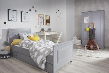 Dwudrzwiowa szafa na ubrania oraz łóżko z szufladą w pokoju chłopca z drewnianą podłogą i miejscem do nauki