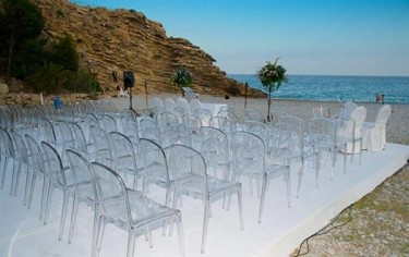 Transparentne krzesła na tarasie z białym dywanem podczas uroczystości zaślubin