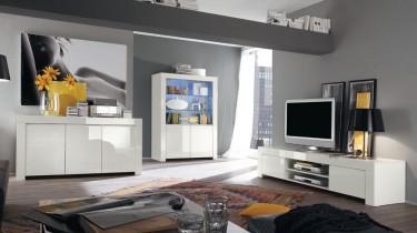 Białe meble w wysokim połysku jako uzupełnienie dużego, nowoczesnego salonu z szarymi ścianami