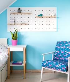 Skandynawski stolik nocny z drewnianymi nogami na tle niebieskiej ściany