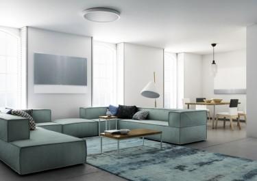 Modułowe meble wypoczynkowe w otwartym salonie z jadalnią na tle białych ścian