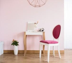 Biała toaletka z lusterkiem na drewnianych nogach i tapicerowane krzesło w stylu retro