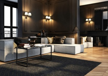 Tapicerowane sofy modułowe i stolik industrialny w ciemnym salonie z lampami ściennymi i drewnianą podłogą
