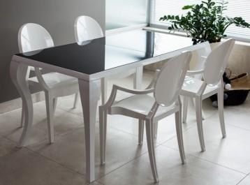 Elegancki stół ze szklanym blatem w towarzystwie designerskich białych krzeseł z podłokietnikami w minimalistycznej jadalni