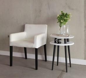 Stolik kawowy i tapicerowany fotel w jednakowej kolorystyce na tle betonowej ściany