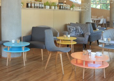 Kolorowe stoliki kawowe w stylu skandynawskim w nowoczesnym wnętrzu kawiarnianym