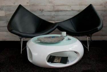 Skórzane fotele w towarzystwie lakierowanego stolika ze szklanym blatem w salonie z drewnopodobną ścianą