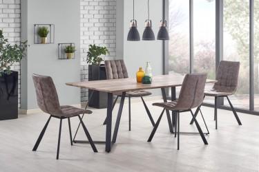 Pikowane krzesła w zestawie ze stołem na metalowej podstawie w nowoczesnej jadalni z wiszącymi lampami i dużym oknem