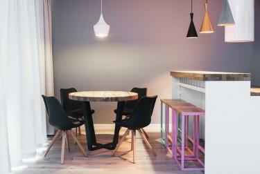 Okrągły stół z drewnianym blatem w stylu industrialnym w towarzystwie krzeseł na drewnianych nogach