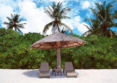 Brązowy leżak na kółkach z regulowanym oparciem i kawowy stolik z tworzywa sztucznego na niebiańskiej plaży