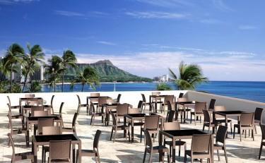 Brązowe krzesła do kawiarni bez podłokietników i stoły na czterech nogach ze szklanym blatem