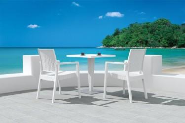 Białe tarasowe krzesła z podłokietnikami oraz stolik kawowy z kwadratowym blatem