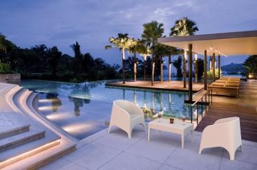 Białe fotele ogrodowe z obszernym siedziskiem oraz stolik kawowy z prostokątnym blatem na czterech nogach
