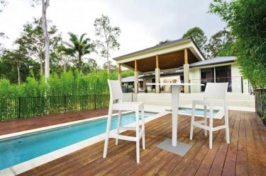 Ogrodowy stolik na jednej nodze oraz białe hokery z wysokim oparciem i podnóżkiem