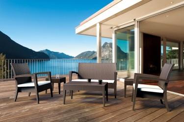Sofa i fotele tarasowe z podłokietnikami i poduszkami na siedzisku oraz stolik kawowy z tworzywa sztucznego