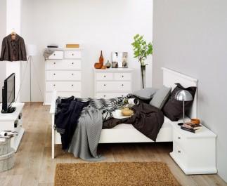 Białe łóżko z wysokim wezgłowiem uzupełnione szafką nocną oraz komody z szufladami i szafka RTV