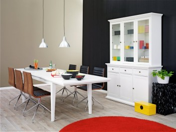Rozkładany biały stół dla sześcioosobowej rodziny oraz kredens z szufladami i przeszklonymi drzwiami